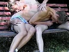 Horny fellas throating each other on bench in park