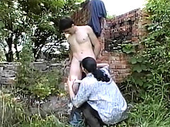 Twink sucking his buddy's dick outside in an alley